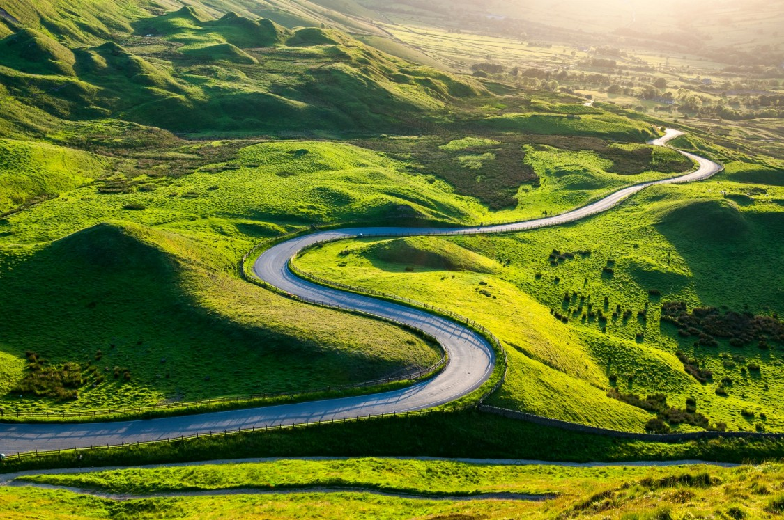 a windy road through the green grass fields of the country