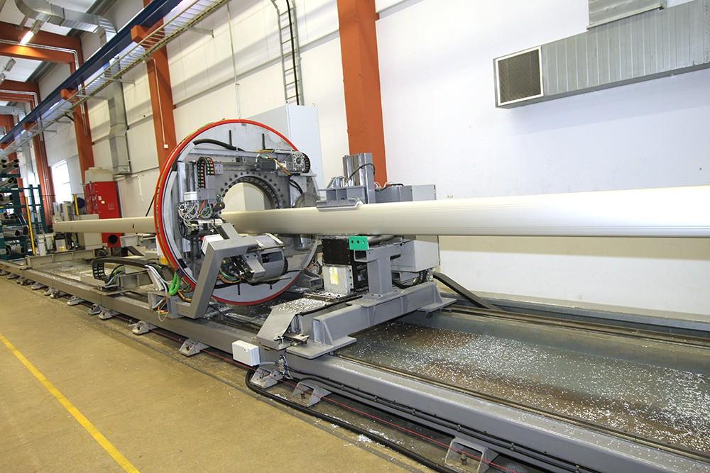 Skrymmande produktion – men kompakt och snygg lösning! Maskinen har rörliga klampar i ändarna och en fast klamp på bearbetningsenheten som körs i Z- och Y-axlar, där de två Z-axlarna har magasin med åtta verktygsplatser. Kapklinga sitter på motsatt sida. Maskinen jobbar sig fram i fönster, 1 900 mm åt gången. Servomotorer positionerar till lämpliga positioner. Den gamla spindelmotorn och kapmotorn är frekvensstyrda men använder Siemens motormoduler.